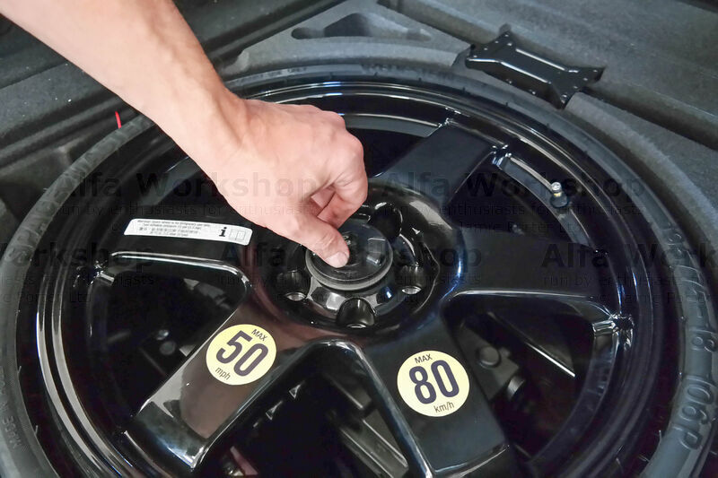 <p>Undo the retaining screw in the hub of the space saver and lift the wheel from the boot.